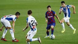 Striker Barcelona, Lionel Messi, berusaha melewati pemain Espanyol pada laga La Liga di Stadion Camp Nou, Rabu (8/7/2020). Barcelona menang 1-0 atas Espanyol. (AP/Joan Monfort)