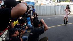 Sejumlah fotografer memotret seorang model yang berpose di Jalan MH Thamrin, Jakarta, Minggu (19/7/2015). Momen Jakarta sepi akibat banyak yang mudik, dimanfaatkan fotografer untuk memotret model. (Liputan6.com/Johan Tallo)
