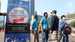 Badan Pajak dan Retribusi Daerah Pemprov DKI membuka gerai Samsat Keliling Car Free Day, Jakarta, Minggu (21/10). Layanan pembayaran pajak Surat Tanda Nomor Kendaraan (STNK) bisa dilakukan tanpa membawa salinan atau BPKB. (Liputan6.com/Angga Yuniar)