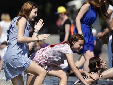 Gadis-gadis Rusia bermain di kolam air mancur di Taman Gorky, Moskow (7/6). Memasuki musim panas, sebagian warga Moskow menghabiskan waktu di taman untuk berjemur atau bermain air di kolam air mancur. (AFP Photo/Alexander Nemenov)