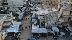 Pemandangan udara saat warga Suriah membeli produk makanan di pasar menjelang buka puasa pada hari kedua Ramadhan, di kota Ariha yang dilanda perang, di provinsi Idlib, Kamis (15/4/2021). Mereka menjalankan Ramadhan di antara lautan reruntuhan bekas konflik gencatan senjata. (Omar HAJ KADOUR/AFP)