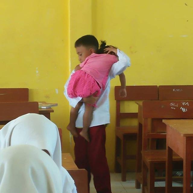 Seorang anak yang membawa adiknya ke sekolah di Sampang, Madura, Jawa Timur/copyright facebook.com/Leendya Putry Kurniawati