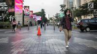 Seorang wanita berjalan mengenakan masker pelindung untuk menghindari polusi udara buruk di Jakarta, Rabu (17/7/2019). Dinkes DKI menyarankan masyarakat untuk menggunakan masker saat beraktivitas untuk mencegah dampak polusi udara pada tubuh. (Liputan6.com/Faizal Fanani)