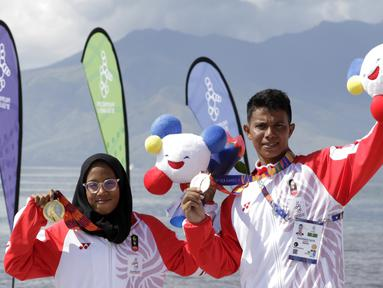Atlet modern pentathlon, Muhammad Taufik dan Dea Salsabila, berpose usai meraih medali pada nomor beach triathle individual SEA Games 2019 di Subic, Jumat (6/12). Taufik meraih perunggu dan Dea meraih emas. (Bola.com/M Iqbal Ichsan)