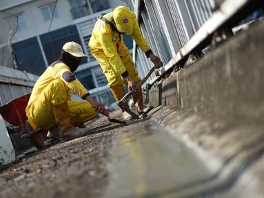 FOTO: Petugas Bina Marga memerbaiki lantai Jembatan Penyeberangan Orang (JPO) yang berlubang di kawasan Tebet, Jakarta, Kamis (27/8/2020). Perbaikan dilakukan guna meningkatkan kenyamanan bagi pejalan kaki yang melintas. (Liputan6.com/Immanuel Antonius)