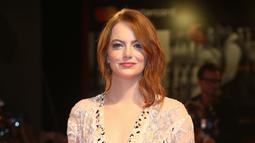 """Aktris Emma Stone berpose saat tiba menghadiri pemutaran film """"The Favorite"""" selama Festival Film Venice ke-75 di Venice Lido, Italia, (30/8). Emma Stone tampil cantik dengan gaun transparan warna krem. (AP Photo/Joel C Ryan)"""