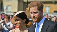 Pangeran Harry dan Meghan Markle menghadiri pesta kebun Istana Buckingham di London, Selasa (22/5). Meghan Markle meninggalkan tampilan rambut messy bun andalannya, untuk beralih gaya rambut sleek dengan bun di samping. (Dominic Lipinski/Pool via AP)