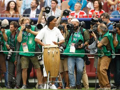Legenda sepakbola Brasil, Ronaldinho dikelilingi oleh para fotografer saat menabuh jenis musik gendang, bongo pada seremonial final Piala Dunia 2018 di Stadion Luzhniki, Minggu (15/7). Kehadiran Ronaldinho membuat suporter antusias. (AP/Francisco Seco)