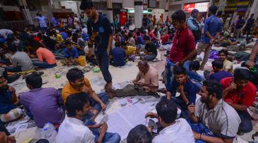 Orang-orang Bangladesh bermain kartu sambil menunggu dalam antrean untuk mendapatkan tiket  mudik lebaran di Stasiun Kereta Kamalapur, Dhaka, Kamis (23/5/2019). Pemudik Bangladesh rela antre berjam-jam dan bahkan menunggu jauh hari sebelum pembukaan loket tiket. (MUNIR UZ ZAMAN/AFP)
