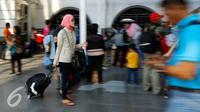 Seorang pemudik membawa barang bawaan menuju pintu masuk Stasiun Pasar Senen, Jakarta, Rabu (23/9/2015). PT KAI mencatat tiket keberangkatan ke sejumlah daerah di Jawa bagian timur telah terjual hampir 100 persen. (Liputan6.com/Yoppy Renato)