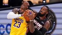 Pebasket Miami Heat, Jae Crowder, berebut bola dengan pebasket Los Angeles Lakers, LeBron James, pada gim keempat final NBA di Lake Buena Vista, Rabu (7/10/2020). Lakers menang dengan skor 102-96. (AP Photo/Mark J. Terrill)