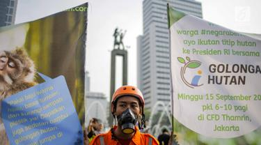 Anggota Walhi Jakarta menggelar aksi melawan asap dan peduli satwa saat car free day (CFD) di kawasan Bundaran HI, Jakarta, Minggu (15/9/2019). Walhi menuntut pemerintah segera menyelesaikan permasalahan kebakaran hutan yang berdampak buruk bagi manusia dan lingkungan. (Liputan6.com/Faizal Fanani)