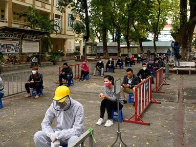 Penduduk memakai masker mengantre dengan tertib saat akan mengikuti pengujian Covid-19 di pusat pengujian dekat rumah sakit Bach Ma, Hanoi, Vietnam (31/3/2020). Warga Vietnam antusias mengikuti tes Covid-19 dengan tertib di tengah masifnya penyebaran Covid-19 di dunia. (AFP/Manan Vatsyayana)