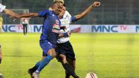 Duel penyerang Arema FC, Kushedya Hari Yudo, dan pemain Persela Lamongan, Eky Taufik, di laga Grup B Piala Gubernur Jatim 2020, Kamis (13/2/2020). (Bola.com/Iwan Setiawan)