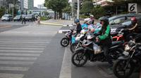 Pengendara sepeda motor melanggar garis berhenti lampu merah Jalan MH Thamrin, Jakarta, Kamis (4/10). Masih banyak pengendara yang melanggar dan tidak mengindahkan penerapan tilang elektronik. (Liputan6.com/Faizal Fanani)