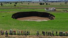 Pemandangan udara dari sinkhole yang ditemukan oleh petani di lahan pertanian di Santa Maria Zacatepec, negara bagian Puebla, Meksiko pada 30 Mei 2021. Lubang yang penuh dengan air itu pada hari Minggu lebarnya hanya sekitar 30 meter. (JOSE CASTAÑARES/AFP)