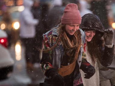 Pejalan kaki melintasi persimpangan di Times Square saat badai salju di New York City (7/3). Badai salju kedua yang melanda New York dalam waktu seminggu ini diperkirakan akan membawa angin kencang. (Drew Angerer/Getty Images/AFP)