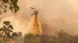 Helikopter menjatuhkan penghambat laju api ke kobaran api dekat Wooroloo, di Perth, Australia, Selasa (2/1/2021). Kebakaran hutan tak terkendali di sebuah wilayah di sebelah timur laut Perth telah menghancurkan puluhan rumah dan kemungkinan mengancam lebih banyak lagi. (Evan Collis/DFES via AP)