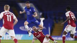 Striker Chelsea, Olivier Giroud (atas) melompat menghindari tekel bek Arsenal, Rob Holding dalam laga lanjutan Liga Inggris 2020/2021 pekan ke-35 di Stamford Bridge, London, Rabu (12/5/2021). Chelsea kalah 0-1 dari Arsenal. (AP/Adam Davy/Pool)