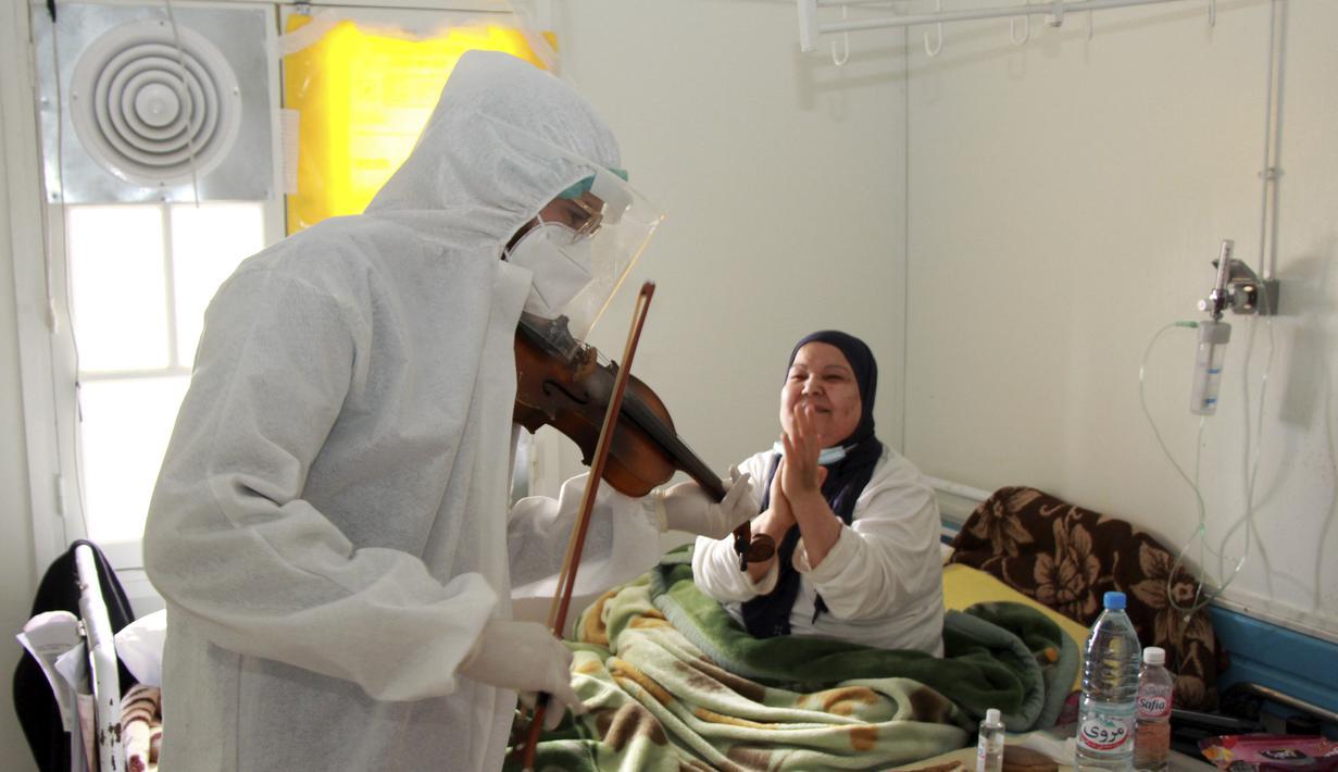Dr. Mohamed Salah Siala memainkan biola untuk pasien di bangsal COVID-19 rumah sakit Hedi Chaker di Sfax, Tunisia, 20 Februari 2021. Ketika pemain 25 tahun itu memutuskan memainkan biolanya, dia mendapat pujian karena meningkatkan semangat pasien yang terisolasi dan membutuhkan senyuman. (AP Photo)