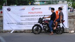 Warga membaca spanduk sosialisasi penutupan perlintasan kereta di Jalan Angkasa, Jakarta, Minggu (15/10). Penutupan secara permanen perlintasan KA di Jalan Angkasa akan dilakukan pada 3 November mendatang. (Liputan6.com/Helmi Fithriansyah)