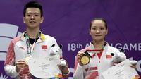 Pebulu tangkis ganda campuran China Zheng Siwei (kiri) dan Huang Yaqiong (kanan) berpose usai penyerahan medali emas nomor perorangan Asian Games 2018 di Istora Senayan, Jakarta, Senin (27/8). ANTARA FOTO/INASGOC/Puspa Perwitasari/18/tom/18.