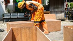 Petugas PPSU membuat peti jenazah di Kantor Kelurahan Kayu Putih, Jakarta, Selasa, (6/7/2021). Kelurahan Kayu Putih berinisiatif membuat peti jenazah dilatar belakangi warganya yang terkendala ketersediaan peti saat angka kematian COVID-19 meningkat di DKI. (Liputan6.com/Faizal Fanani)