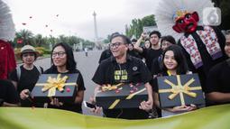 Aktivis yang tergabung dalam Amnesty Internasional Indonesia membawa bingkisan untuk pemerintah saat menggelar aksi di depan Istana Negara, Jakarta, Selasa (10/12/2019). Momen pemberian bingkisan untuk pemerintah dinamakan Aksi Penyerahan Pesan Perubahan (PENA). (Liputan6.com/Faizal Fanani)