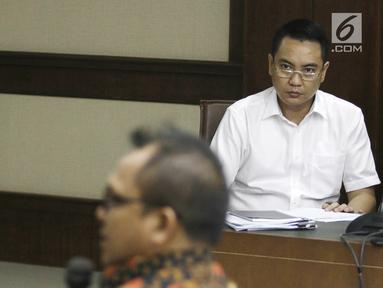 Terdakwa mantan anggota Komisi I DPR, Fayakhun Andriadi (kanan) mendengarkan keterangan saksi Sekretaris DPD Golkar Basri Baco dalam sidang dugaan suap Bakamla di Pengadilan Tipikor, Jakarta, Rabu (12/9). (Liputan6.com/Herman Zakharia)