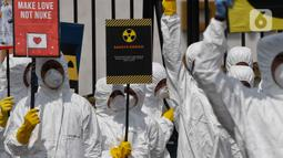 Aktivis Greenpeace saat menggelar aksi damai kreatif menolak energi nuklir di depan Gedung DPR, Jakarta, Jumat (13/3/2020). Aksi ini bagian dari peringatan sembilan tahun bencana Fukushima. (Liputan6.com/Johan Tallo)