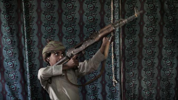 Mantan tentara cilik, Kahlan (12) mendemonstrasikan bagaimana cara menggunakan senjata di Marib pada Juli 2018 (AP Photo/Nariman El-Mofty)