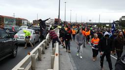 Pekerja konstruksi dan demonstran menghadiri protes terhadap peraturan Covid-19 di Melbourne (21/9/2021). Ribuan orang membuat kekacauan dan bentrok dengan polisi di kota dan mengambil alih jalan raya utama Melbourne saat protes terjadi. (AFP/Con Chronis)