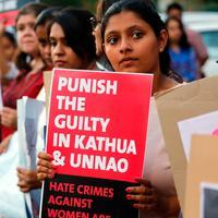 Sejumlah wanita India menunjukkan poster saat aksi protes kasus perkosaan di Ahmadabad, India (16/4). Protes ini dipicu karena perkosaan dan pembunuhan yang menimpa seorang gadis berusia 8 tahun. (AP Photo / Ajit Solanki)