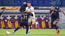 Penyerang AS Roma, Borja Mayoral berebut bola dengan bek Ajax Amsterdam, Lisandro Martinez pada leg kedua perempat final Liga Europa di Olimpico, Jumat (16/4/2021) dini hari WIB. AS Roma melaju ke semifinal Liga Europa musim ini setelah bermain imbang 1-1 lawan Ajax. (Fabio Rossi/LaPresse via AP)
