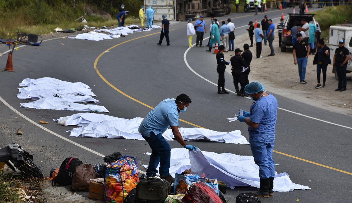 Tim forensik menutupi tubuh penumpang yang tewas dalam kecelakaan bus yang menabrak truk trailer di Gualan, Guatemala (21/12/2019). Kecelakaan tersebut menewaskan sedikitnya 21 orang dan menyebabkan belasan orang luka-luka. (AP Photo/Carlos Cruz)