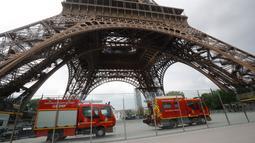 Kendaraan petugas penyelamat terparkir di bawah Menara Eiffel, Paris, Senin (20/5/2019). Menara Eiffel ditutup bagi pengunjung setelah seseorang pria berusaha memanjat bangunan ikonik tersebut tanpa izin. (AP/Michel Euler)