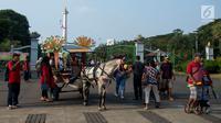 Pengunjung naik delman melintas di depan Monas ketika hari libur Lebaran hari kedua, Jakarta, Kamis (6/6/2019). Libur hari Lebaran dimanfaatkan sejumlah warga dari Jabodetabek untuk berpergian ke tempat wisata yang ada di Jakarta. (merdeka.com/Imam Buhori)