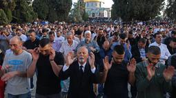 Umat Muslim melaksanakan sholat Idul Fitri di luar masjid Kubah Batu di kompleks masjid Al-Aqsa, Yerusalem Tua (13/5/2021).  Rentetan tembakan roket dari Gaza dan serangan udara Israel yang mematikan sebagai pembalasan. (AFP/Ahmad Gharabli)