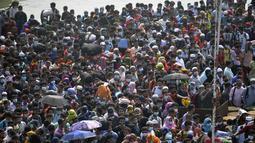 Orang-orang menunggu untuk menaiki kapal feri menuju kampung halaman menjelang perayaan Idul Fitri di tengah pandemi Covid-19 di Munshiganj, Bangladesh pada 9 Mei 2021. Ratusan orang bergegas untuk pulang ke rumah sehingga dapat berkumpul dengan keluarga pada momen Lebaran. (Munir Uz zaman/AFP)
