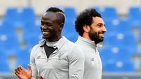 Senyum pemain Liverpool, Mohamed Salah (kanan) dan Sadio Mane saat sesi latihan di Stadion Olimpico, Roma, Italia (1/5). Liverpool unggul 5-2 menghadapi AS Roma pada leg pertama semifinal Liga Champions. (Ettore Ferrari / ANSA via AP)