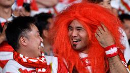 Seorang fans mengenakan rambut palsu tertawa dengan rekannya sebelum pertandingan antara Rusia dan Jepang pada pembukaan Rugby World Cup Pool A  di Stadion Tokyo (20/9/201). Rugby World Cup diselenggarakan dari 20 September hingga 2 November 2019. (AFP Photo/Toshifumi Kitamura)