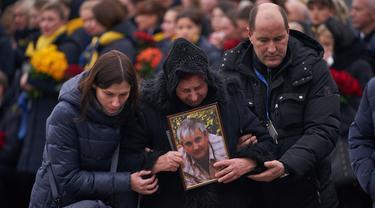 Keluarga korban menghadiri upacara penghormatan 11 warga Ukraina yang tewas dalam insiden jatuhnya pesawat Ukraine International Airlines di Iran (8/1) lalu, Bandara Boryspil Kiev, Ukraina, Minggu (19/1/2020). Pesawat tersebut jatuh oleh rudal pasukan IRGC. (Ukrainian Presidential Press Service/AFP)