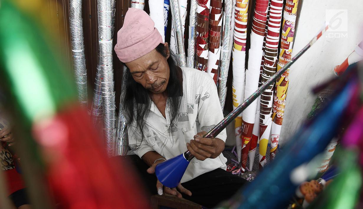 Pengrajin menyelesaikan pembuatan terompet di kawasan Glodok, Jakarta, Selasa (25/12). Menjelang tahun baru terompet konvensional tersebut dijual dengan harga dari Rp 5000 hingga Rp 10.000 tergantung ukuran dan jenisnya. (Liputan6.com/Herman Zakharia)