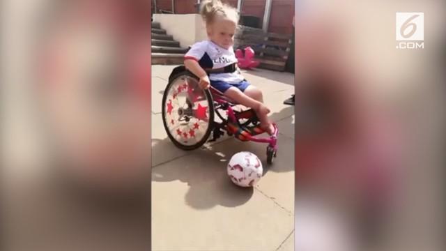Meski memiliki keterbatasan yang mengharuskannya duduk di kursi roda, bocah berusia tiga tahun ini tetap semangat bermain bola.
