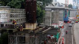 Pekerja proyek pembangunan kereta ringan atau Light Rail Transit (LRT) rute Cawang-Dukuh Atas sedang beristirahat di kawasan Gatot Subroto, Jakarta, Kamis (18/1). (Liputan6.com/JohanTallo)