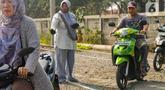 Neng Mulyani atau Bu Neng (tengah) mengatur lalu lintas di perlintasan kereta yang berada di Batuceper, Tangerang, Jumat (15/11/2019). Selama 8 tahun, wanita paruh baya ini mengabdikan waktunya untuk menjaga perlintasan. (Liputan6.com/Magang/Andika Zulfikar)