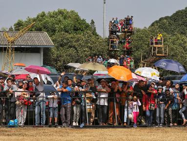 Sejumlah warga mengenakan payung saat menyaksikan perayaan HUT ke-74 TNI di Lanud Halim Perdanakusuma, Jakarta Timur, Sabtu (5/10/2019). Warga rela panas-panasan dan berdesak-desakan untuk menyaksikan perayaan HUT ke-74 TNI. (Liputan6.com/JohanTallo)