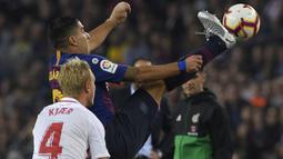 Striker Barcelona, Luis Suarez, berebut bola dengan bek Sevilla Simon Kjaer, pada laga La Liga Spanyol di Stadion Camp Nou, Barcelona, Sabtu (20/10). Barcelona menang 4-2 atas Sevilla. (AFP/Lluis Gene)