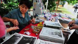 Warga membeli surat kabar setelah sehari meninggalnya mantan PM Singapura, Lee Kuan Yew, Singapura, Selasa (24/3/2015). Lee meninggal pada hari Senin (23/3) di usia 91 tahun dan wajahnya menghiasi berbagai media cetak Singapura. (AFP PHOTO/Mohd FYROL)