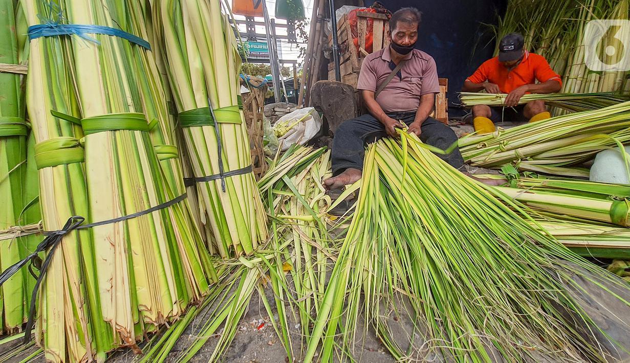 Pedagang membuat kulit ketupat dari anyaman daun kelapa muda (janur) di Pasar Pondok Labu, Jakarta Selatan, Kamis (30/7/2020). Memasuki Hari Raya Idul Adha, pedagang musiman kulit ketupat menjualnya dengan harga Rp 5 ribu hingga Rp 15 ribu. (Liputan6.com/Fery Pradolo)